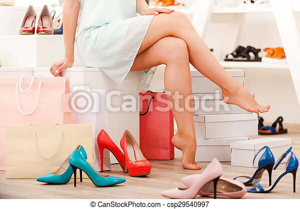 Hard choice. Close-up of young barefoot woman sitting in shoe store while different shoes laying near her