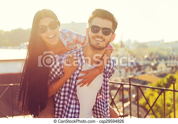 Young and in love. Happy young man carrying his girlfriend on shoulders while having fun together on the roof