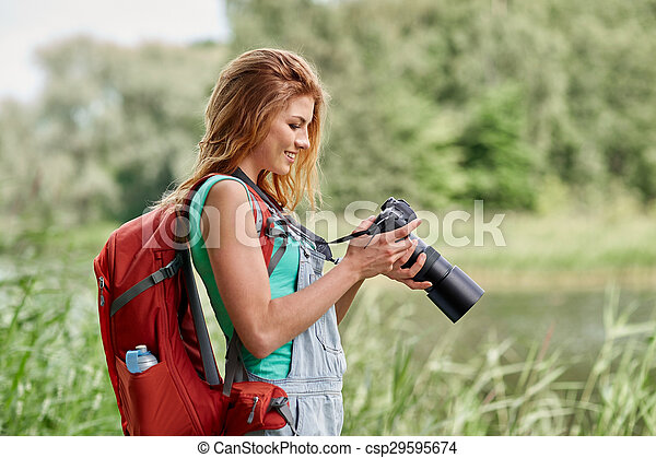 happy woman with backpack and camera outdoors