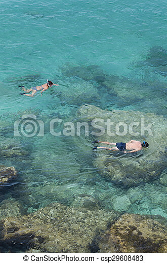 Two people do snorkeling near the rocks
