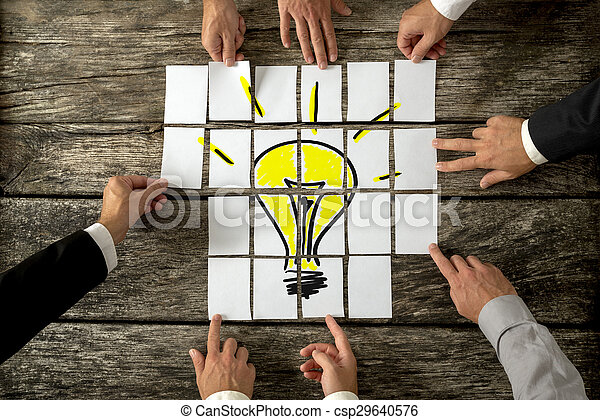 High Angle View of Businessmen Hands Touching White Papers Arranged on a Rustic Wooden Table forming a yellow light bulb