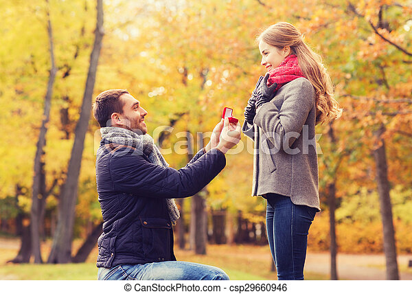 smiling couple with engagement ring in gift box
