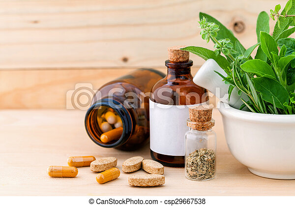 Alternative health care fresh herbal , dry and herbal capsule with mortar on wooden background.