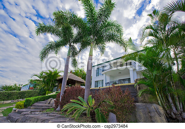 Garden with palms and Bali hut in front of waterfront mansion - csp2973484