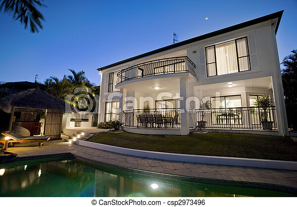 Luxurious mansion exterior at dusk overlooking pool - csp2973496
