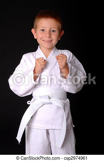 Young boy in karate outfit making fighting movement