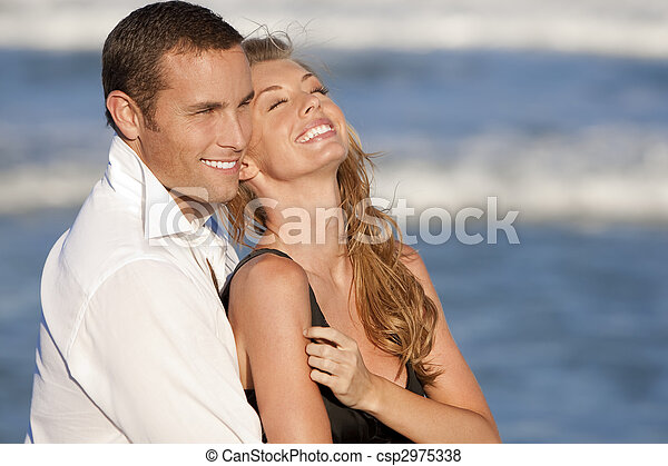 Man and Woman Couple Laughing In Romantic Embrace On Beach - csp2975338