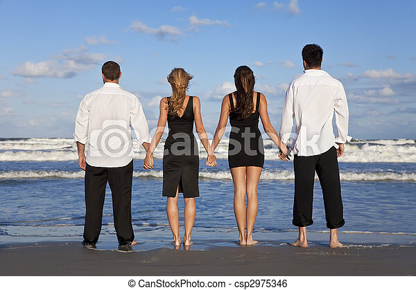 Four Young People, Two Couples, Holding Hands On A Beach - csp2975346