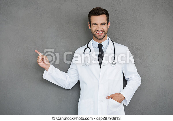 Showing new ways of healing. Smiling young doctor in white uniform looking at camera and pointing away while standing against grey background