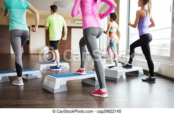 close up of people working out with steppers in gym