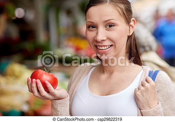 happy woman holding tomato at street market