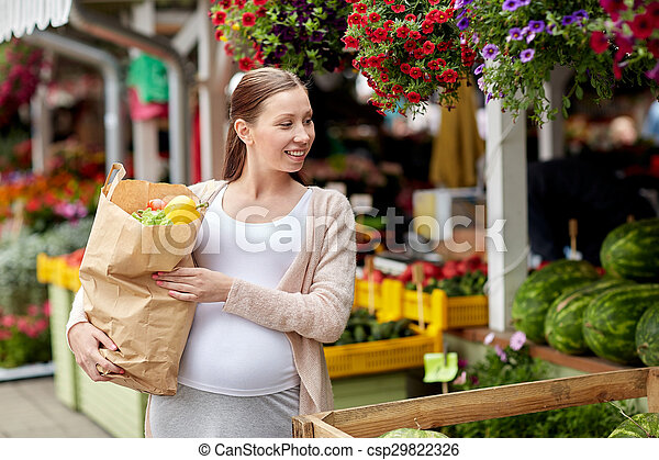 pregnant woman with bag of food at street market