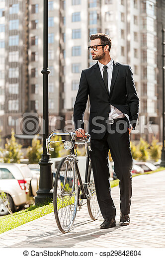 Getting to work by bike today. Full length of handsome young businessman rolling his bicycle while walking outdoors