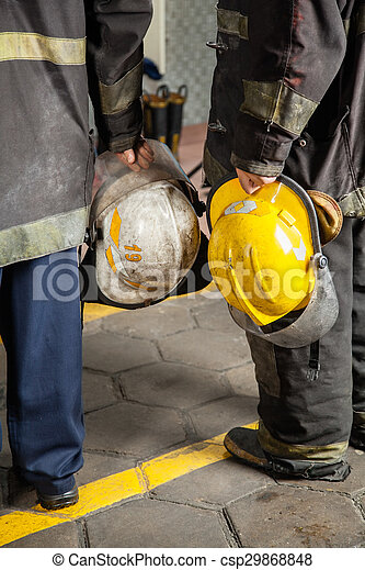 Low section rear view of firemen holding helmets at fire station