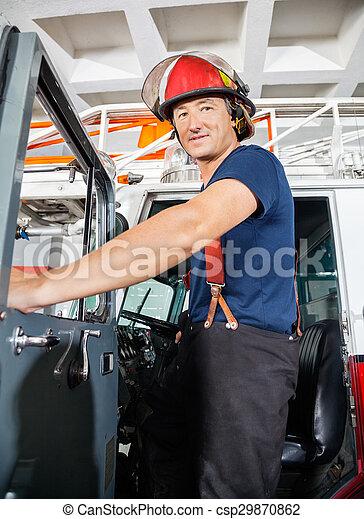 Smiling Fireman Standing On Truck