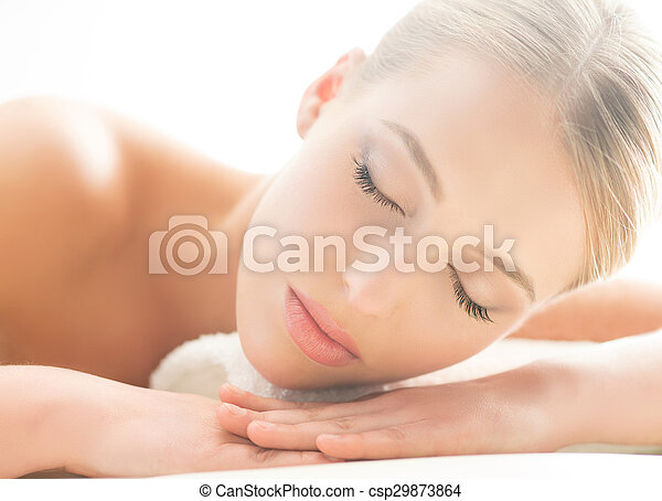 Beautiful young woman having leisure lying in a mat in spa.