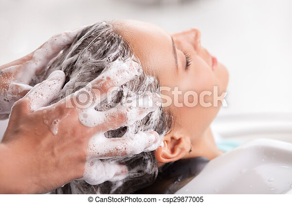 Cheerful young woman has her hair washed in beauty shop