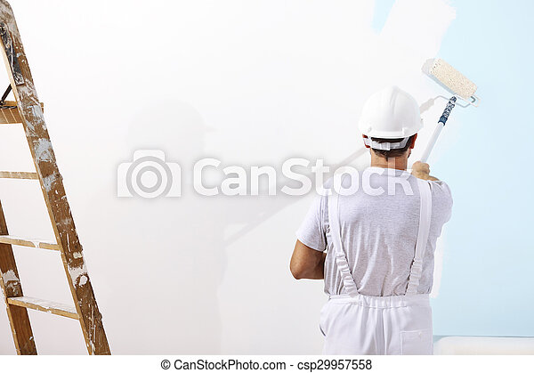 painter man at work with a paint roller on the wall