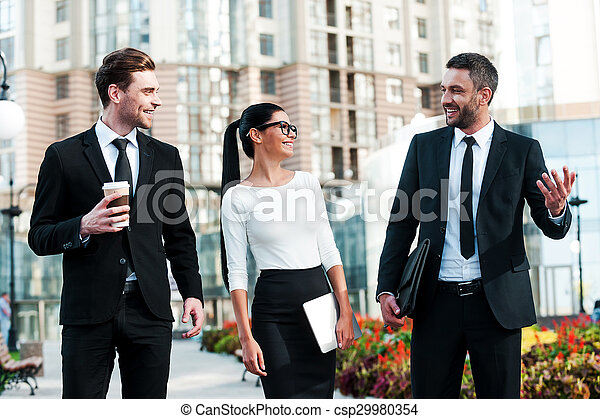 Quick briefing before meeting. Three cheerful young business people talking to each other while walking outdoors
