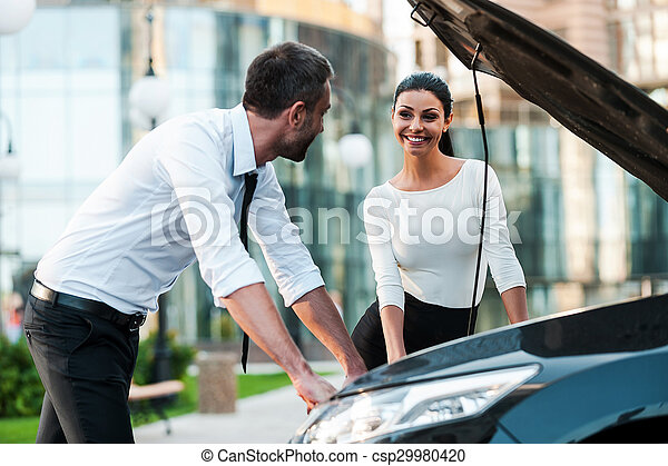 He is always ready to help. Two smiling young business people looking at each other while leaning at the opened vehicle hoodof the car