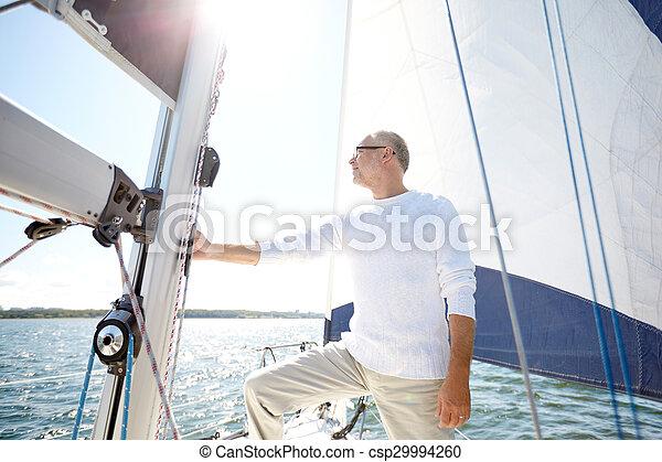 senior man on sail boat or yacht sailing in sea