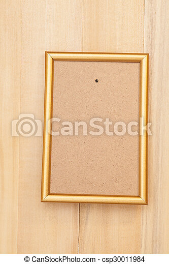 Empty golden picture frame on wooden background
