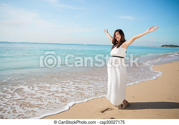 Asian pregnant woman enjoying in the beach with open arms