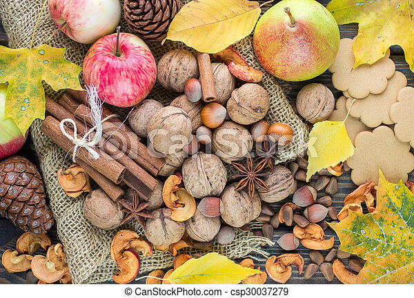 Apples, pears, walnuts, pine nuts, hazelnuts, cinnamon and star anise on the table