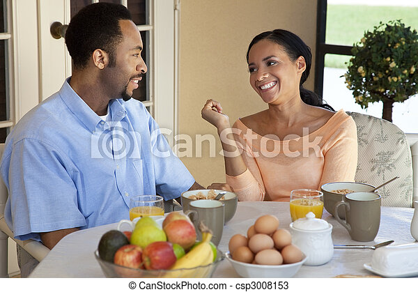 A happy African American man and woman couple in their thirties sitting outside having a healthy breakfast - csp3008153