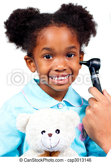 Smiling little girl attending medical check-up holding a teddy bear isolated on a white background - csp3013146