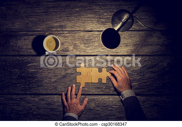 Overhead view of businessman working late at night at his rustic textured desk to have finnaly came to a conclusion or solution about the future of his business