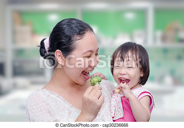 mother and her daughter eating vegetables