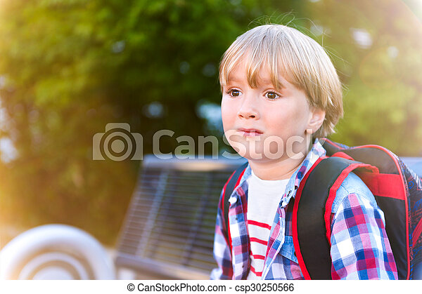 Cute little boy resting on the bench after school, wearing backpack