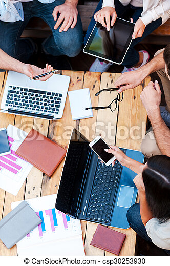 Creativity in action. Top view of four young people working together while sitting at the wooden table