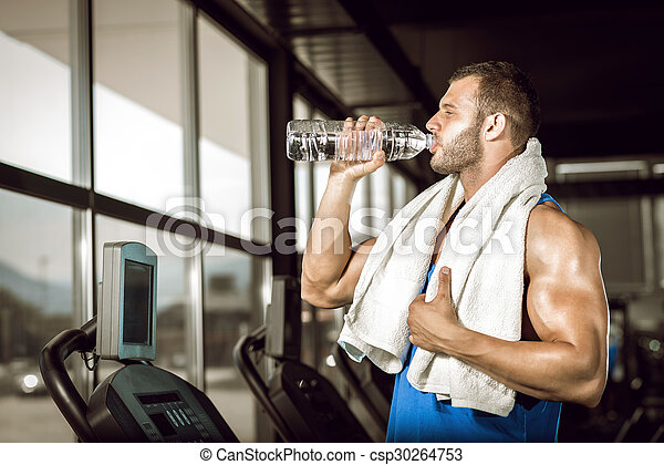 Young man drinking water in gym