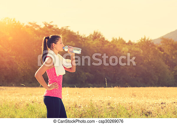 Attractive female taking a break after jogging, holding bottle of water - csp30269076