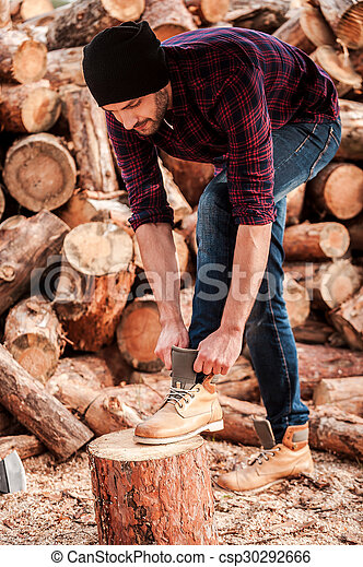 Getting ready to work. Full length of confident young forester adjusting his shoes while leaning at the log