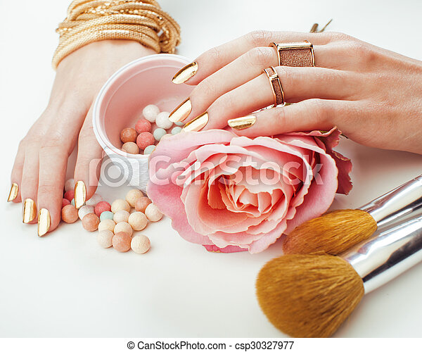 woman hands with golden manicure many rings holding brushes, make up artist stuff stylish and pure