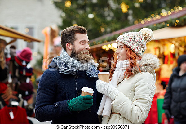 happy couple drinking coffee on old town street