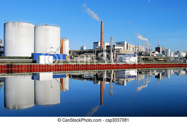 Industrial site with smoking stacks reflected in a river - csp3037081