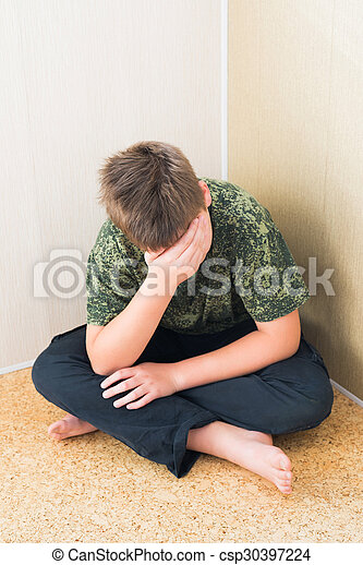 Boy teenager with depression sitting in the corner of room
