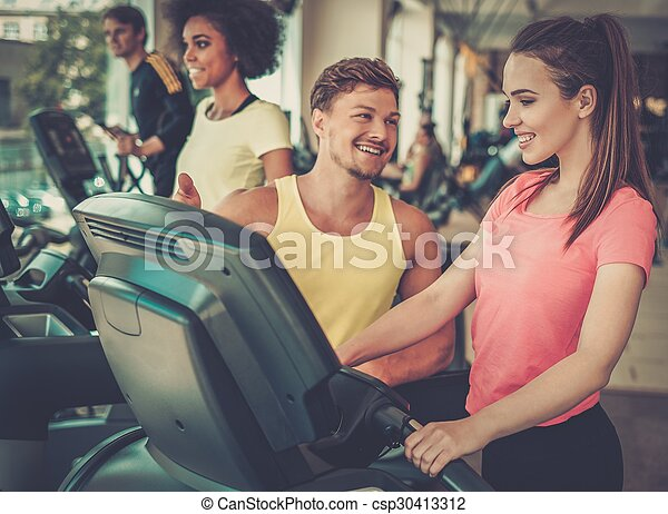 Trainer explaining how to use treadmill - csp30413312