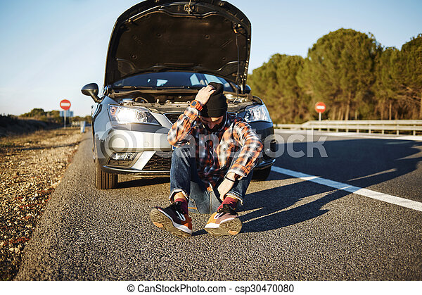 Car man sits near the broken automobile, sad and upset. Young ma