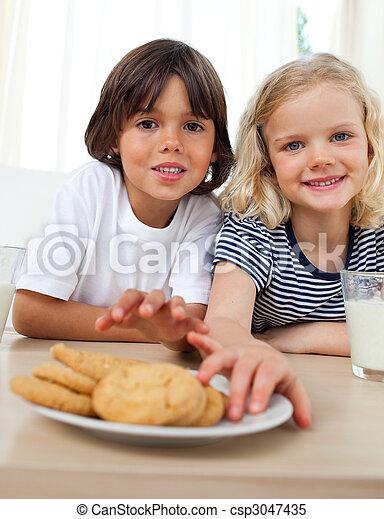 Cute siblings eating biscuits  - csp3047435