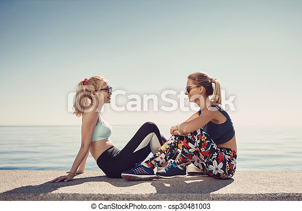 Sport fitness girls relaxing after training outdoor. Young couple talking sitting in waterfront after running and training exercise outside in summer. Caucasian and asian sports women models.