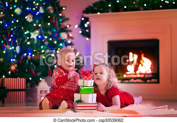 Kids opening Christmas presents at fire place