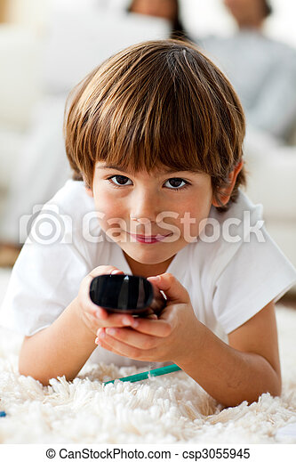 Smiling little boy holding a remote lying on the floor  - csp3055945