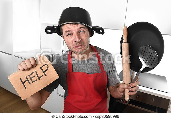 funny man holding pan with pot on head in apron at kitchen askin