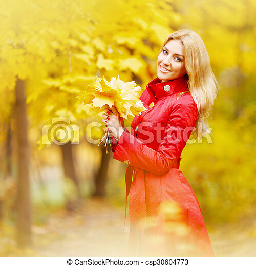 Woman with bunch of maple leaves