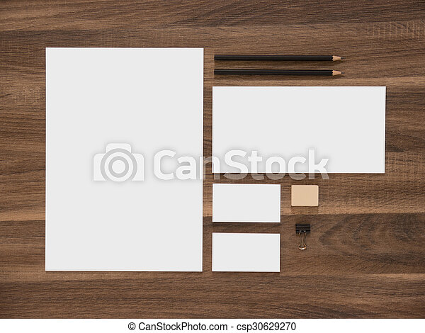 Letterhead, envelope and blank business cards on wooden desk.